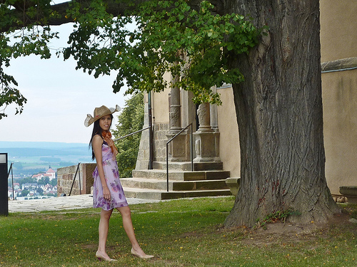 melancholy woman under the tree in summer outfit