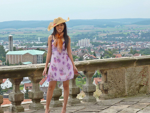 smiling woman wearing summer dress and hat