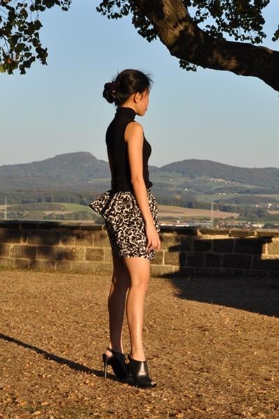 black turtleneck top, black skirt and peep-toe pumps